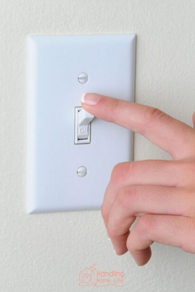 house cleaning tips:  woman turning off light switch