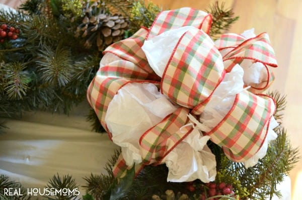 bow of a christmas wreath with tissue paper stuffed into the bow loops so it holds shape in storage